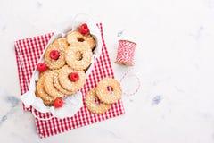 De koekjes met suikerdalingen in een metaal werpen met frambozen klaar om voor vakantie of gift te verfraaien Stock Afbeelding