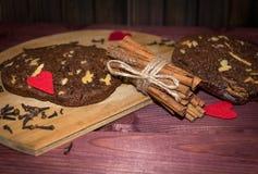 De koekjes van de okkernootchocolade met pijpjes kaneel op houten plankenachtergrond Royalty-vrije Stock Afbeeldingen