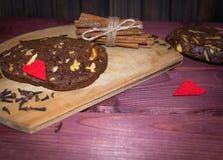 De koekjes van de okkernootchocolade met pijpjes kaneel op houten plankenachtergrond Royalty-vrije Stock Afbeelding