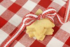De koekjes van de ster met lint op geruite doek Stock Afbeeldingen