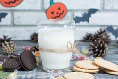 De koekjes van Halloween met een glas melk Stock Afbeeldingen