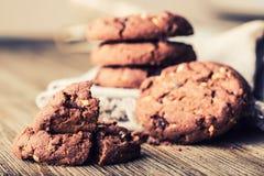 De koekjes van het chocoladekoekje Chocoladekoekjes op wit linnenservet op houten lijst Het schot van chocoladeschilferkoekjes op Stock Foto