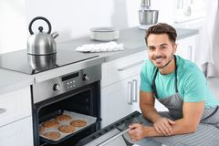 De koekjes van het jonge mensenbaksel in oven royalty-vrije stock foto