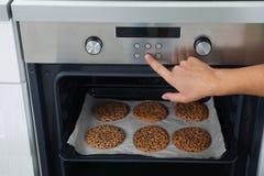 De koekjes van het jonge mensenbaksel in oven thuis royalty-vrije stock foto's