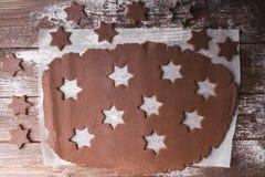 De Koekjes van Kerstmis van het baksel Ontwikkel het deeg om sterren op een houten achtergrond te verwijderen Royalty-vrije Stock Foto