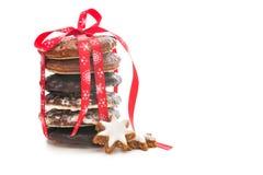 De koekjes van Kerstmis op wit met rood lint Stock Afbeeldingen