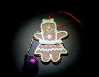 De koekjes van mensenkerstmis met Kerstmisballen door een flitslicht op bovenkant op zwarte worden verlicht die Royalty-vrije Stock Fotografie