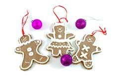 De koekjes van mensenkerstmis met Kerstmisballen op wit Royalty-vrije Stock Afbeeldingen