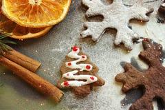 De koekjes van prentbriefkaarkerstmis in de vorm van vlokken, met droge sinaasappel, pijpjes kaneel en anijsplant worden verfraai royalty-vrije stock fotografie