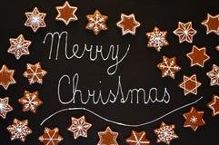 De koekjessterren en sneeuwvlokken van peperkoekkerstmis met wit suikerglazuur met tekst vrolijke Kerstmis op zwarte achtergrond Royalty-vrije Stock Foto