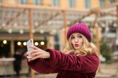 De koele blondevrouw kleedde zich in warme kleren makend selfie bij B Stock Foto's
