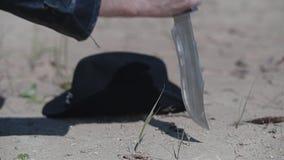 De koele kerel in een regenjas en dreadlocks zet ter plaatse zijn hoed in de woestijn en begint iets met een mes op gr. te trekke stock videobeelden