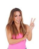 De koele vrouw kleedde zich in roze die het teken van overwinning met de hand maken Stock Afbeeldingen