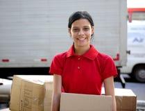 De koerier of de verhuizer die van de levering cardboards leveren Stock Afbeeldingen