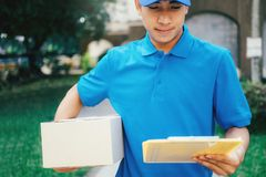 De koerier die van de leveringsdienst zich voor het huis met dozen bevinden stock foto's