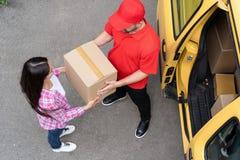 De koerier geeft leveringspakket aan jonge vrouw Hoogste mening royalty-vrije stock afbeeldingen