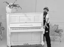 De koerier levert meubilair, beweging uit, verhuizing De lader beweegt pianoinstrument Mens met baardarbeider in helm en stock foto's