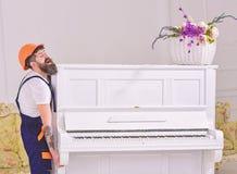 De koerier levert meubilair, beweging uit, verhuizing Mens met baard omhoog arbeider in helm en overallliften, inspanningen zich  royalty-vrije stock afbeelding