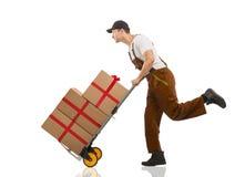 De koerier loopt - het karretje: pakketten en giften Stock Foto