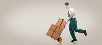 De koerier loopt - het karretje: pakketten en giften Stock Afbeeldingen