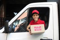 De koerier van de levering in vrachtwagen het overhandigen pakket