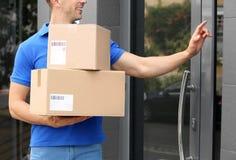 De koerier van de leveringsdienst met pakketten in handen die deurbel bellen stock foto