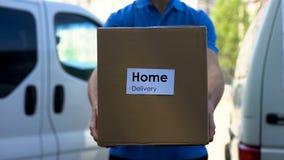 De koerier van de thuisbezorgingsdienst in de eenvormige doos van het holdingskarton, het uitdrukkelijke verschepen stock afbeeldingen