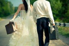 De koffers van de het paarholding van de jonggehuwde contant geld Stock Foto