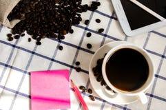 De koffie, de koffiebonen, de telefoons, de potloden en de notitieboekjes zijn op het bureau royalty-vrije stock afbeeldingen