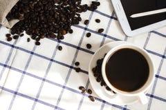 De koffie, de koffiebonen, de telefoons, de potloden en de notitieboekjes zijn op het bureau stock afbeelding
