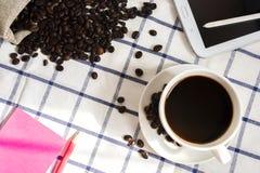 De koffie, de koffiebonen, de telefoons, de potloden en de notitieboekjes zijn op het bureau stock fotografie