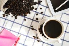 De koffie, de koffiebonen, de telefoons, de potloden en de notitieboekjes zijn op het bureau royalty-vrije stock foto