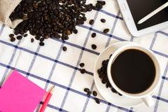 De koffie, de koffiebonen, de telefoons, de potloden en de notitieboekjes zijn op het bureau royalty-vrije stock afbeelding