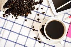 De koffie, de koffiebonen, de telefoons, de potloden en de notitieboekjes zijn op het bureau stock afbeeldingen