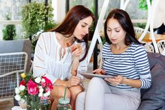 De koffie koopt online meisjestablet twee jonge vrouwen Internet de digitale witte gelukkige cocktail van de zomerbloemen bladere royalty-vrije stock foto