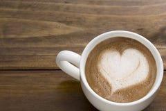 De koffie latte roomt in hartvorm af op hoogste koffiemok op het werkbureau Stock Foto