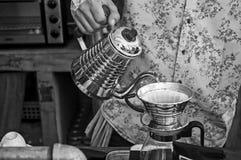De koffie met giet over techniek op zwart-witte toon Stock Afbeeldingen