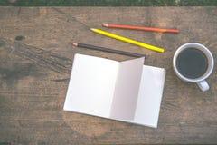 De koffie, potloden, notitieboekjes wordt geplaatst op de lijst vanochtend royalty-vrije stock afbeelding