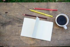 De koffie, potloden, notitieboekjes wordt geplaatst op de lijst vanochtend stock fotografie