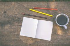 De koffie, potloden, notitieboekjes wordt geplaatst op de lijst vanochtend royalty-vrije stock foto