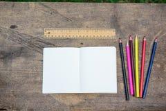 De koffie, potloden, notitieboekjes wordt geplaatst op de lijst vanochtend stock foto