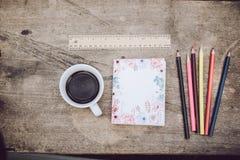 De koffie, potloden, notitieboekjes wordt geplaatst op de lijst vanochtend royalty-vrije stock foto's