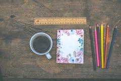 De koffie, potloden, notitieboekjes wordt geplaatst op de lijst vanochtend stock afbeelding