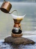 De koffie van de handdruppel op de rotsen bij de rivier Royalty-vrije Stock Afbeeldingen