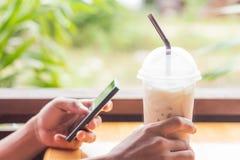 De koffie van de handgreep en mobiele gebruiks slimme telefoon stock afbeelding