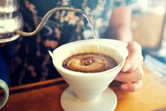 De Koffie van de handdruppel, het gietende warme water van Barista op geroosterd koffiedik royalty-vrije stock foto