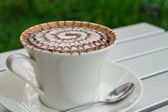 De koffie van het ontwerppatroon in een witte kop Stock Foto