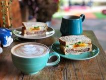 De koffie van de Lattekunst op de houten lijst, Heerlijk Gezond Ontbijt met Zwarte koffie en latte kunstkoffie stock foto's