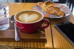 De koffie van de Lattekunst in rode kop Stock Afbeeldingen