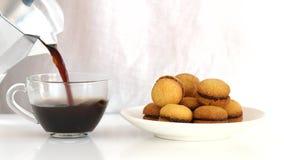 De koffie wordt gegoten in een kop dichtbij de plaat met koekjes